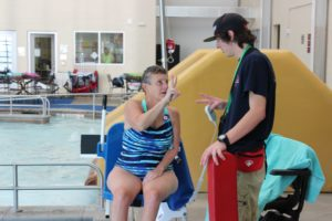 "Linda communicates with MAC Lifeguard manager using hand gestures while he assists her out of the pool. ""Every time that Linda comes in to swim, it immediately changes the mood and brightens our day,"" said Tanner."